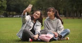 кампус : Two happy asian college girl sitting on the lawn using mobile phone taking selfie together in campus. Стоковые видеозаписи