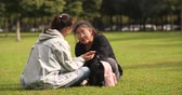 кампус : two asian teen girl sitting on the lawn looking at mobile phone talking together outdoor in the park