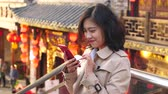 Pretty happy young asian woman using mobile phone video chatting  in the Chinese city of Chengdu at afternoon with traditional Chinese style red lantern