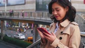 járda : slow motion  of pretty happy young asian woman using mobile phone in the city at afternoon Stock mozgókép
