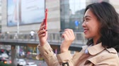 Close up of one pretty happy young asian woman using mobile phone in the city at afternoon