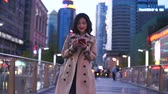 slow motion  of pretty happy young asian woman walking in the city street while using smart phone at evening