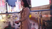 прерыватель : Side view of one pretty happy young asian woman walking in the city street  at evening with mobile phone in hand in slow motion Стоковые видеозаписи