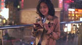 chengdu : slow motion  of pretty happy young asian woman using mobile phone in the city at night