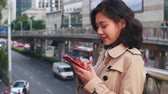 slow motion  of pretty happy young asian woman using mobile phone in the city at afternoon Wideo