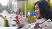 Pretty happy young asian woman using mobile phone video chatting  in the Chinese city of Chengdu at afternoon in slow motion Wideo