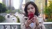 Pretty happy young asian woman using mobile phone  in the Chinese city of Chengdu at afternoon on the overpass with busy road in the background