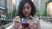 One pretty young asian woman using mobile phone in the city while walking in the street