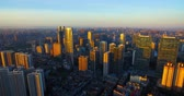 Aerial view of Chengdu city in morning golden sunlight, Downtown Chengdu urban cityscape with old residential and new office buildings together, mountain range in distance big city in Sichuan China