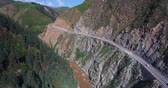 Aerial view of cars driving on winding road in the mountain hill side with stream flowing in the valley, nature drone view landscape of Qilian Mountains of Qinghai Province, China.