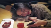 One lovely asian girl leaning on cafe table playing with mobile phone at night. Cute Chinese girl using smartphone indoor, urban lifestyle with mobile technology 4k clip
