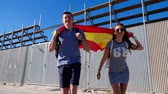 Young happy woman and man running with Spanish flag towards the camera