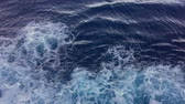 Waves with foam behind a boat in slow motion. Patterns of waves in water. Water surface wake view from the cruise liner
