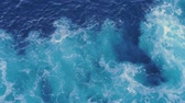 Waves with foam behind a boat. Patterns of waves in water. Water surface wake view from the cruise liner in 4k