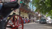 Гавана : HAVANA, CUBA - MAY 13, 2018 - Horse carriage, people and old taxi cars on the streets in 4k