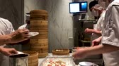蒸し : Chefs cooking Chinese dumplings by the traditional bamboo steamers in a restaurant. Dim Sum chefs working wrapping dumplings at famous restaurant Din Tai Fung. San Deigo, California, USA. February,07,