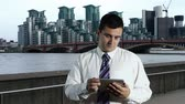 river : Young Businessman Tablet PC at Thames River London