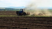The Tractor Plows the Land. Farmer using modern farm tractor with disk harrows for harrowing field. Wideo