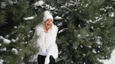 śnieżka : Young pretty woman play with snowballs in forest.