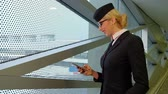 one person only : Stewardess is reading a message on your smartphone and smiles. Woman in stylish sunglasses on her head, on which the white hair gathered into a bun and red lipstick standing at the tinted windows airport and looking at the phone, which is holding in his h Stock Footage