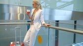 点検 : Shooting from down blonde woman standing drinking coffee in airport. Blond woman stands, holds plastic glass in hall. Young traveler in white suit, grey blouse, classical shoes with bright make up, bl