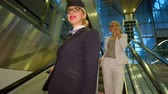 escada rolante : Flight attendant with glasses comes down the escalators and smiling. Woman holds suitcase handle and expect when the lift down to the ground floor. The hall is decorated for the holidays of Christmas fir branches and ornaments. Behind stewardess should a  Stock Footage