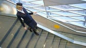 calçados : Slender young stewardess with glasses comes down the stairs airport. She is dressed in a blue uniform with red inserts and slowly moves on the gray stairs in black high heels, leaning on the railing. European lady smiles and goes to his workplace. Sunligh
