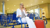um jovem mulher só : Lady in glasses and with luggage speaks by phone the waiting room. In a Russian airport on the blue seat is a young European woman in a light gray pantsuit and blouse, in which the finger elegant expensive ring. Near blonde is a big orange suitcase with e Vídeos