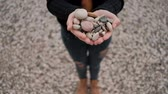 oblázek : Woman standing on shore of lake holding stones in form of heart. Fashionable female in blue ragged jeans in brown shoes black sweater poses for photo session holding pattern of little nice rocks. Focus camera aimed at hands. Body out of focus. Walker with Dostupné videozáznamy