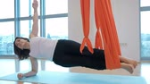 fitness straps : In the gym woman holding horizontal legs in a hammock. Pass fashionable yoga classes in the air. The adult lady rests one hand on the floor, and the second stretches vertically upward. Thus both limbs are passed through orange slings and are on weight. Th