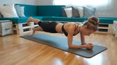 colores fuertes : Young woman in sportswear makes exercise plank on floor indoors. Beautiful blonde in compression T-shirt and black pants is located on gym mat in large bright premise with turquoise sofa and bright pillows. Holding resilient body in one position she conce Archivo de Video