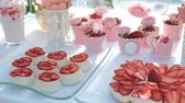 vajas : Sugary appetizers and strawberries on white table outdoor. Light jelly decorated with fresh cut berries, cookies on sticks in carved vases, creamy cheesecakes and strawberries spread out over paper cups with pink little roses. Delicious sweets lie on glas