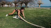 sportwear : Woman in sportswear training pulls thick cable, hawser outdoor. Young athlete in compression top, short black shorts and sneakers workout on green lawn against the backdrop of blue sea and majestic palms. Deciding to practice in fresh air on warm evening,