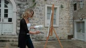 canvas : Woman painter paints picture on easel standing outdoors. Smiling lady draws gouache with black brush on white canvas that is in front of her and occasionally looks at old stone building near which stands. Female dressed in white top and black sweater is k Stock Footage