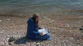 riverbank : Young woman writes sitting on river bank in autumn afternoon. Brunette in hat dressed in blue jacket is conveniently located on small stones at waters edge against backdrop turquoise noisy waves formed by cool wind on sunny Saturday. Lady immersed in rela Stock Footage