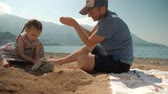 családi élet : Daddy and daughter play gritfully on the seashore in sunny weather. In summer, a man in a baseball cap sits next to a little girl in a long dress and shows how sand is scattered from his hands. Baby looks fascinated and touched by a fine dust. In the back Stock mozgókép