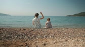 pigtails : Two girls sit on shore and throw stones into water in summer day outdoors.
