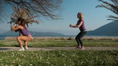 lunge : Two young women doing lunges and squats outdoors in summer day.