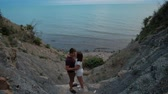 sótão : Attractive couple kissing standing on rock by sea shore on summer day outdoors. They hold hands and gently touch lips, expressing love and emotion. Young man and woman dressed in shorts and t-shirts spend romantic honeymoon in picturesque location, on sto Stock Footage