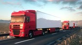 Front-view camera moves towards a convoy of semi trucks driving on a highway into the sunset. Realistic high quality 3d animation. Stock mozgókép
