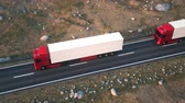 привод : Aerial view of a convoy of semi trucks driving along a desert highway into the sunset. Realistic high quality 3d animation.