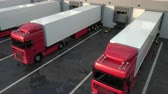 Red semi trucks loading and unloading goods at warehouse dock. Low parallel tracking shot. Seamless loop. Realistic high quality 3d animation. Stock mozgókép