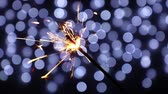 Close up one firework sparkler over black background with defocused blue bokeh, low angle side view Stok Video
