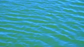 Waves and ripples run in the wind on blue water surface of lake, high angle view, slow motion Vídeos