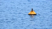 jelző : Close up yellow buoy floating in blue sea water waves and ripples