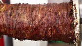 istif : Close up beef meat Turkish doner kebab, Greek gyros or Arabian shawarma roasted and smoked in rotisserie over char grill, low angle side view