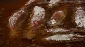Close up cooking deep fried red king mullet fish in hot sizzling oil in big pan high angle view
