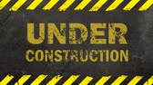 開発 : Black grunge background with painted yellow stripes and under construction sign blinking animation 動画素材