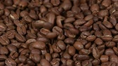 para cima : Close up background of roasted coffee beans falling on table as heap, slow motion