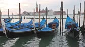 Gondolas moored by Saint Mark square in sunrise. San Giorgio di Maggiore church is in the background (Venice, Italy)